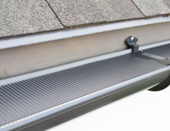 Plastic gutter with a trough on top to prevent debris from entering